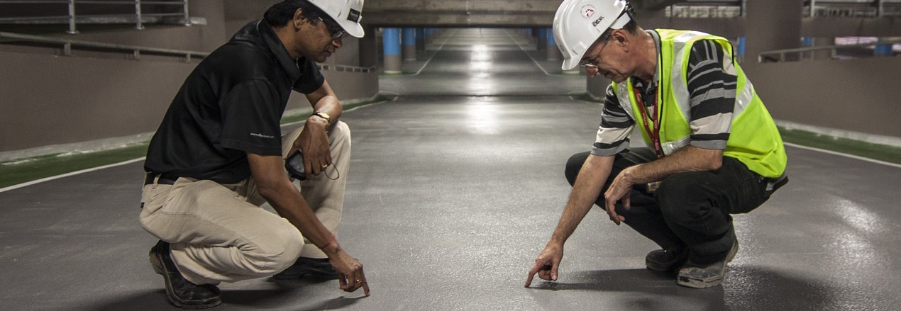 Two men wearing PPE pointing at the floor.